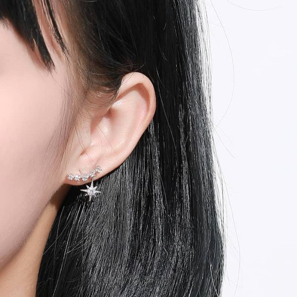 silver temptation earring crawling on the ear with an ornament in the form of a star photographed on a woman's ear at close range