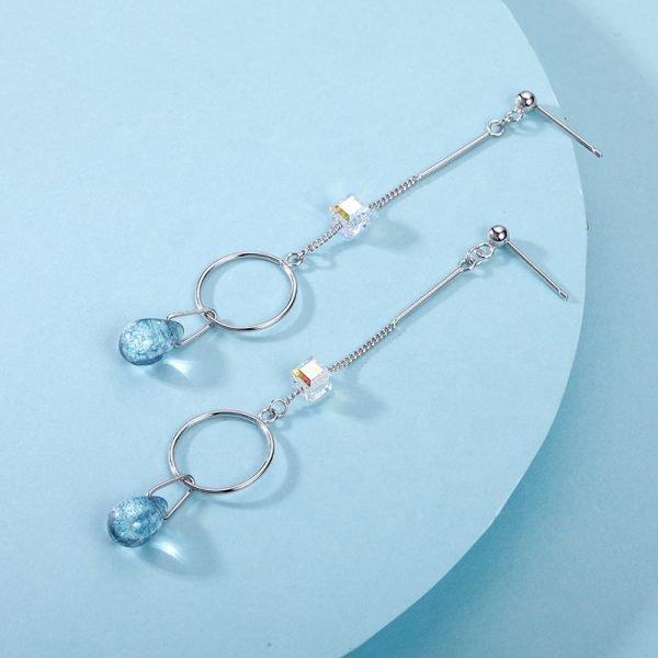 Висящи сребърни обеци с два кристала и халка посредата снимани под ъгъл на свеж син фон