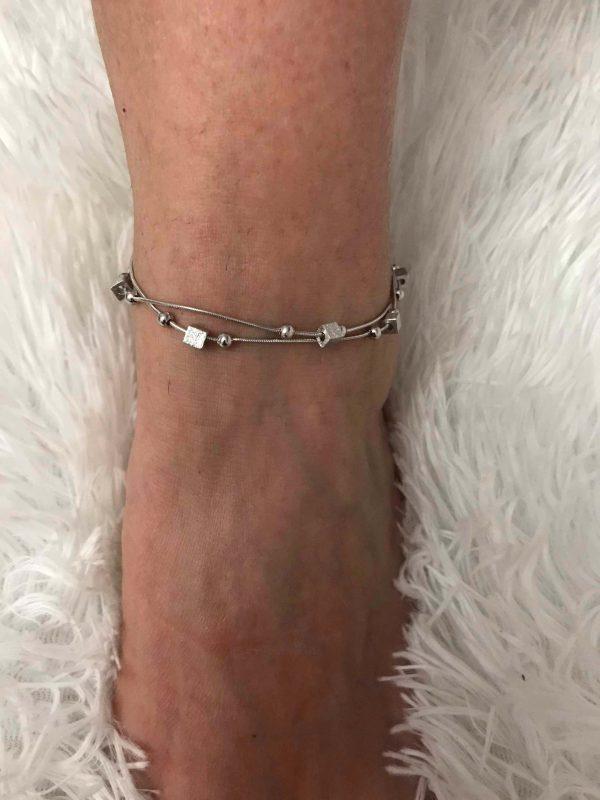 Двойна сребърна гривна за крак с преплетена верижка, мънисто и кубчета на дамски глезен снимана отгоре