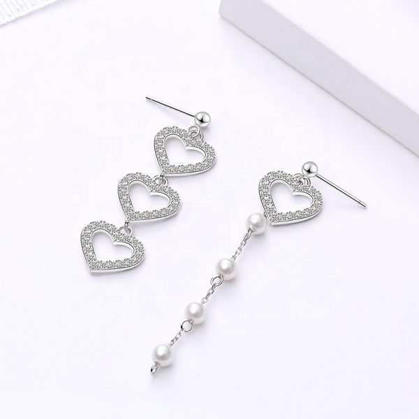 Asymmetrical dangling silver earrings with crystal hearts and pearls photographed close up on white background