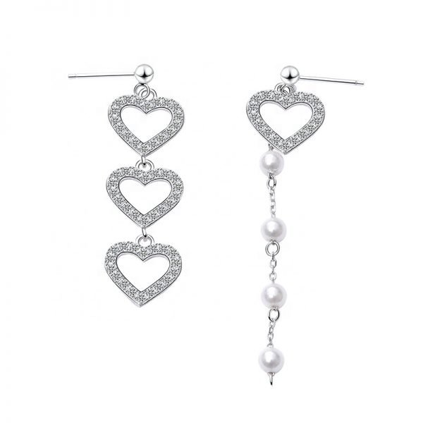 frontal product photography of asymmetrical dangling silver earrings with cubic zirconia crystal hearts and pearls on white background