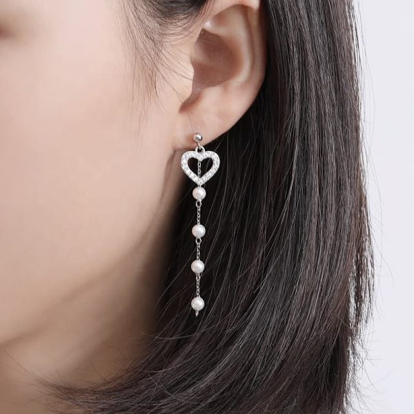 dangling silver earrings with a crystal heart and four small pearls under it on a woman's ear