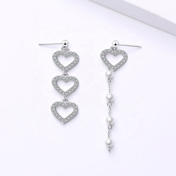 Asymmetrical dangling silver earrings with cubic zirconia crystal hearts and pearls photographed from above on a white background