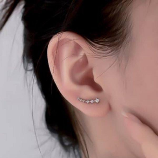 малкият модел сребърни обеци фиби снимани на истинско женско ухо