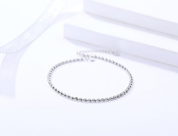 clean silver foot bracelet with oval elements photographed at an angle on a white background