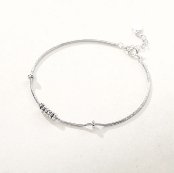 Silver thread bracelet with six oval elements placed side by side at an angle on a white background
