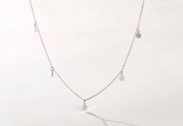 Clear silver necklace with five oval charms photographed frontally on a white background