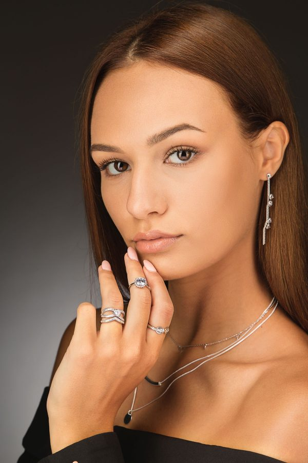 Studio photo of a female model wearing three silver rings with cubic zirconia, dangling earrings and a triple silver necklace on a dark background