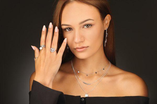 Дамски модел носещ три сребърни пръстена с флорален мотив, придружени от красиви висящи обеци и тройно колие в стил напластяване