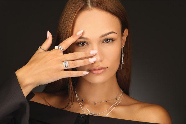 Дамски модел носещ три сребърни пръстена с флорален мотив, придружени от висящи обеци и тройно колие