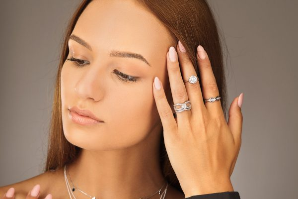 Photo from a slight angle of a ladies model with three shiny silver rings with cubic zircons