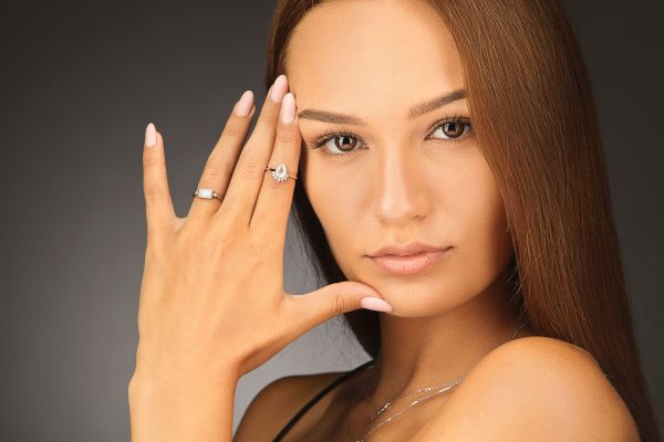 Studio photo on dark background with female model wearing two silver rings with natural moonstone and necklace