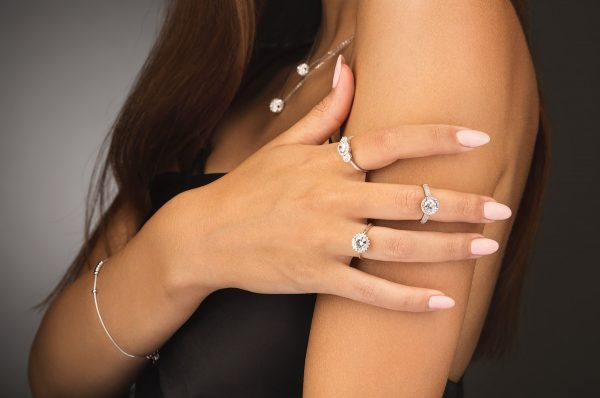 detailed photo of three exquisite silver rings with cubic zirconia on a model