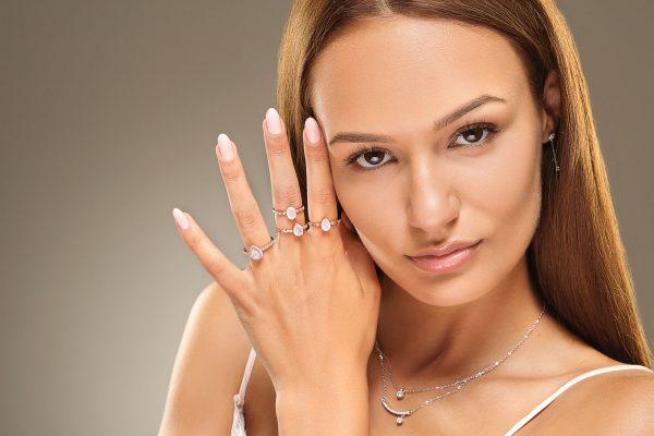 Front shot of a female model wearing four silver moonstone rings and a double silver cubic zirconia necklace