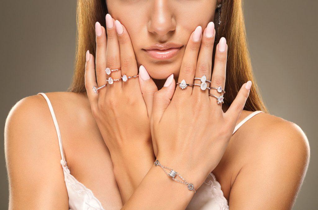 Фронтална снимка на женски модел с 9 сребърни пръстена с естествен лунен камък и сребърна гривна с циркони и овални елементи