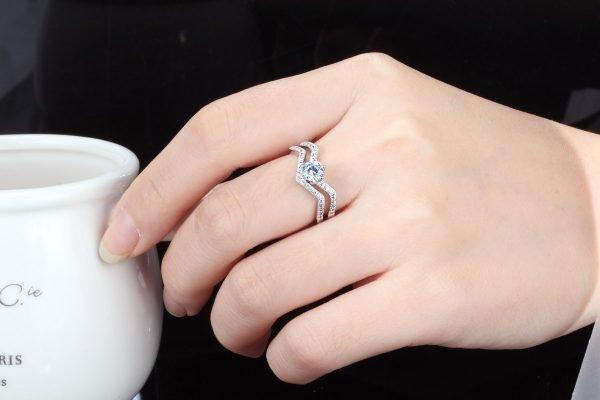дамска ръка с двоен сребърен пръстен с мнозина малки кристали и един по-голям в центъра