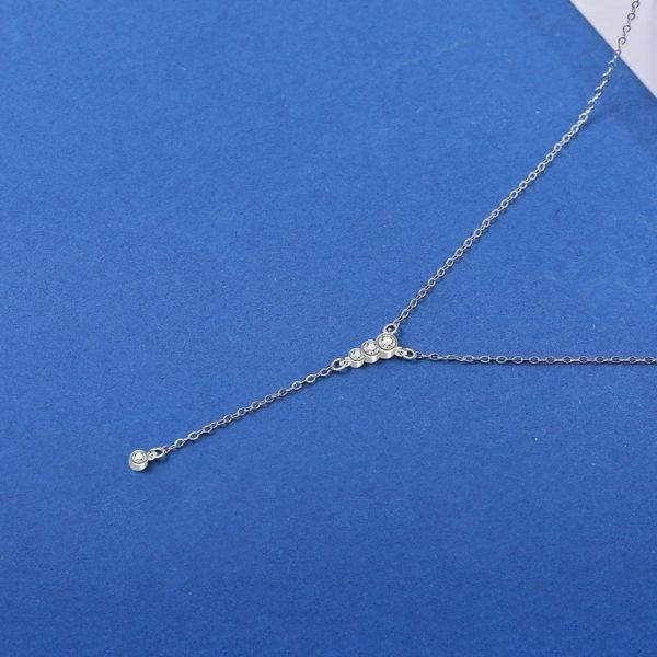 дълго сребърно колие с четири малки кристала снимано отгоре върху синя повърхност
