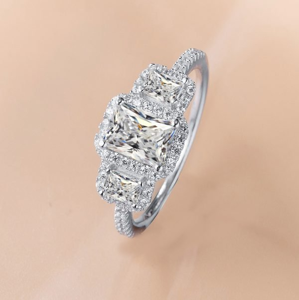 photo of a silver ring with a focus on its three massive cubic zircons and surrounding small crystals