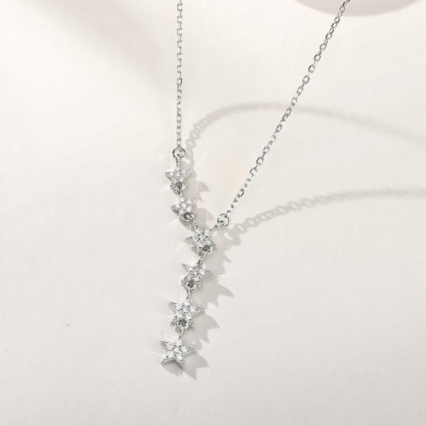 silver necklace with six small crystal stars photographed at a slight angle with focus on the stars