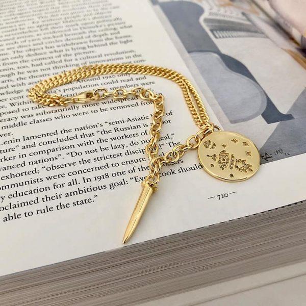 масивна позлатена гривна от две различни плетки и две висулки върху страница от книга
