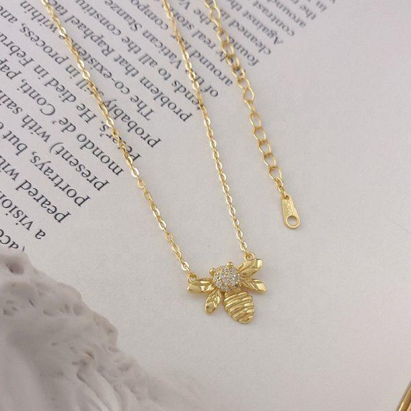 Сребърно колие с 18 каратово златно покритие и класическа плетка под формата на пчела с изящен цирконий в средата и снимано отгоре върху страница от книга