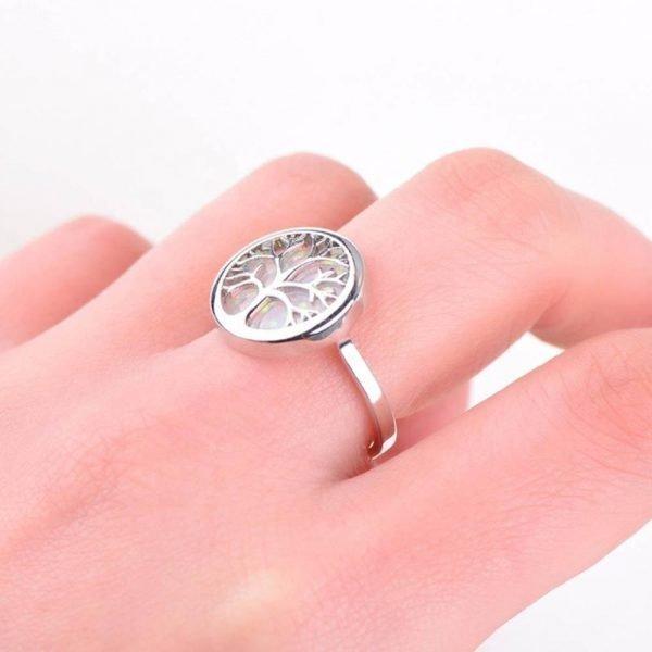 дамска ръка снимана отблизо със сребърен пръстен дървото на живота със синтетичен опал на бял фон