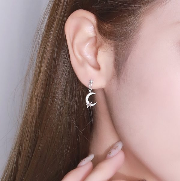 Ladies model with silver earring in the shape of a moon and a small star in the dolant and part
