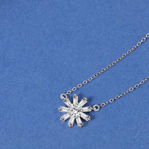 сребърно колие с медальон под формата на слъчноглед снимано на син фон отгоре с фокус върху медальона
