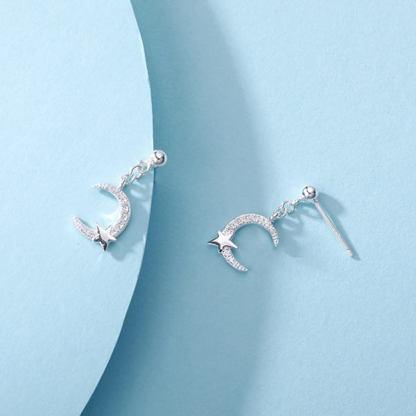 hanging silver earrings with crystals in the shape of a moon and a small star in the bottom part photographed on a blue background