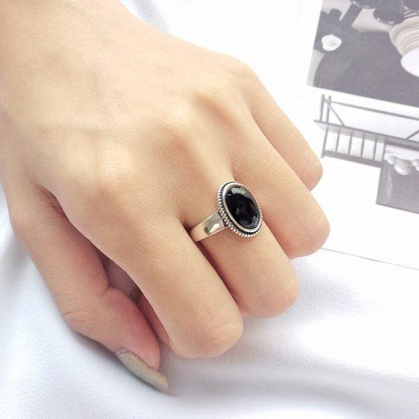 дамска ръка със сребърен пръстен с масивен черен ахат