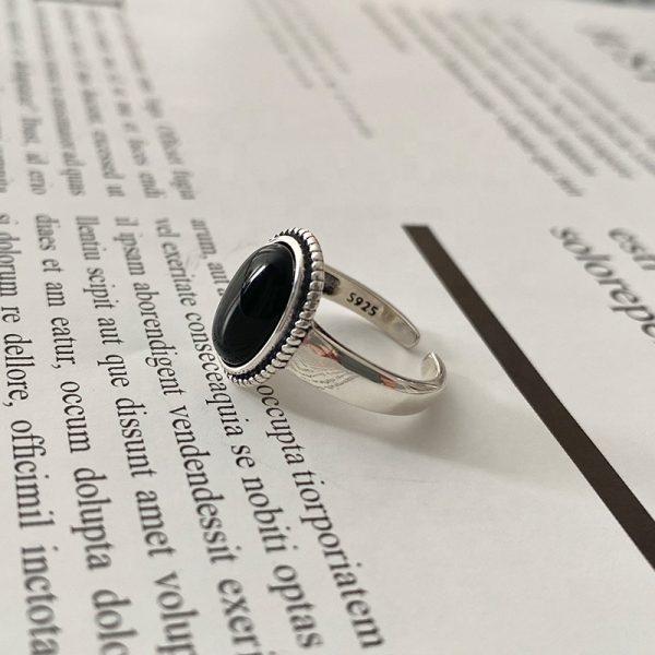 сребърен пръстен с масивен черен ахат сниман отстрани върху страница от книга