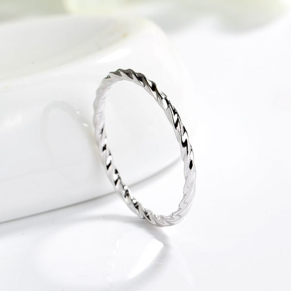 clean silver ring with slight curves photographed from above at a slight angle against a light background