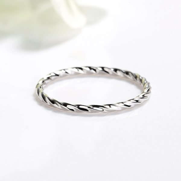 clean silver ring with slight curves set on a white surface