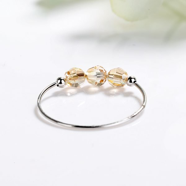 clear silver ring with three light brown crystals