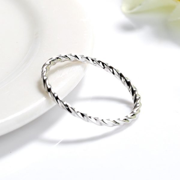 clean silver ring with slight curves placed at a slight angle on a white surface
