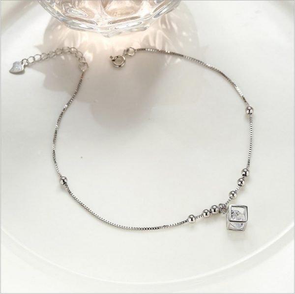 сребърна гривна за крак с мънисто и кубче с малък кристал снимана отгоре