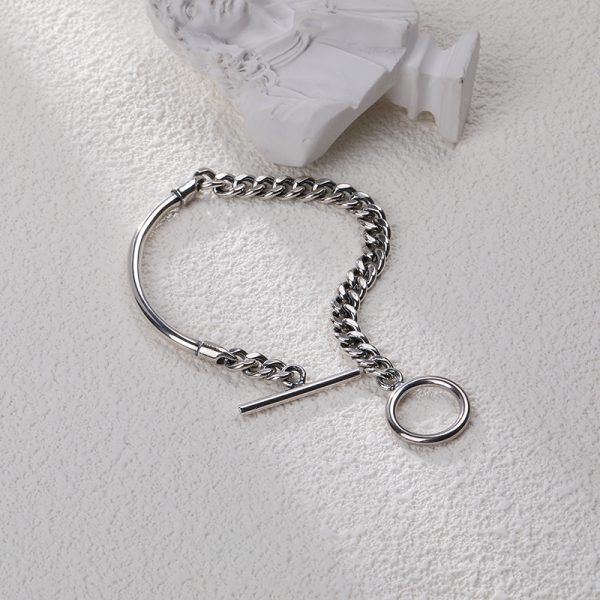 silver bracelet consisting of a solid part, complemented by a massive braid on a white background with a part of the sculptor next to it