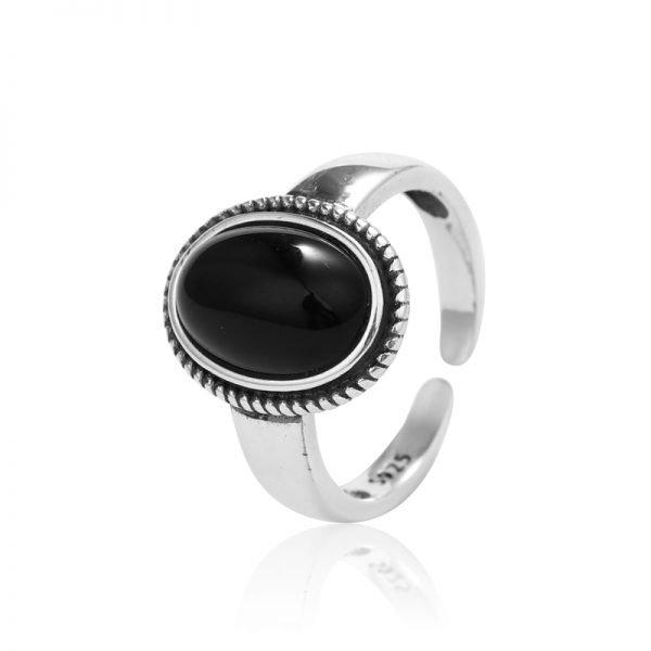 сребърен пръстен с масивен черен ахат сниман отблизо на бял фон