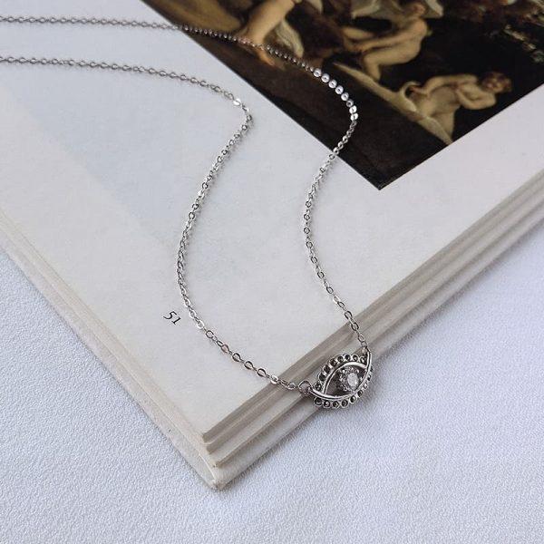 сребърно колие с изчистен медальон назар снимано под ъгъл върху страница от книга
