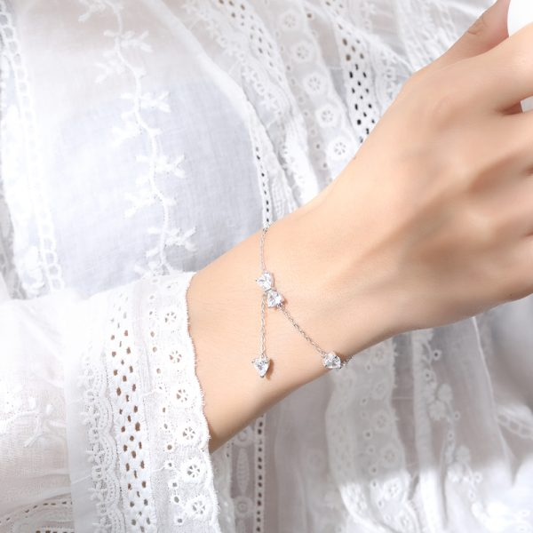 дамска ръка с нежна сребърна гривна с кристална панделка и два други камъка