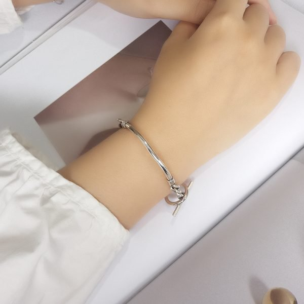 unusual silver bracelet with a solid part, complemented by a massive braid photographed from above on a female hand