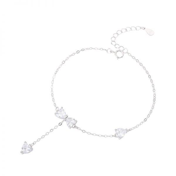 нежна сребърна гривна с кристална панделка и два други камъка снимана отгоре на бял фон