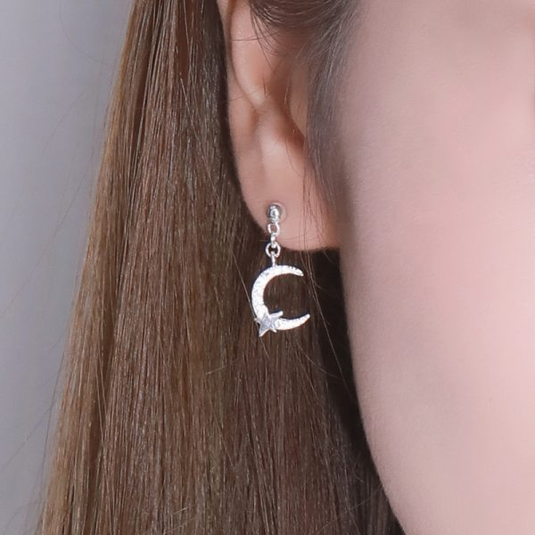 ladies ear with a silver earring in the shape of a moon and a small star in the dolant and part