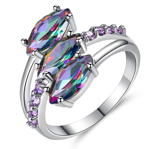 детайлна снимка на сребърен пръстен с три отделни многоцветни камъка топаз на бял фон под лек ъгъл