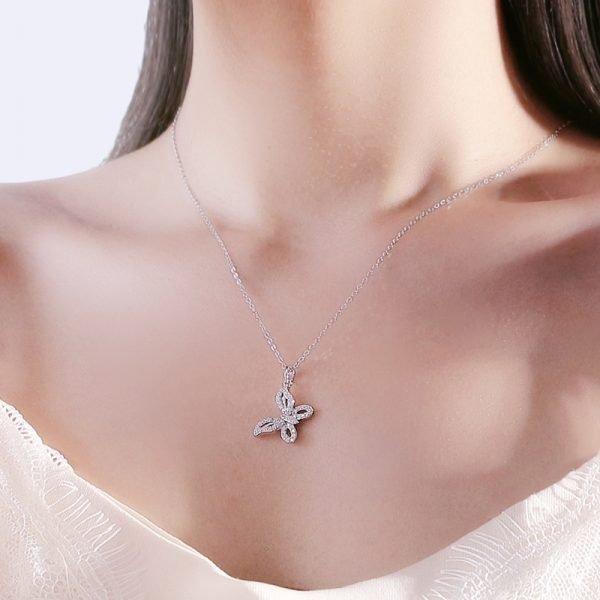 дамски модел носещ сребърно колие с медальон пеперуда обсипан с малки кристали
