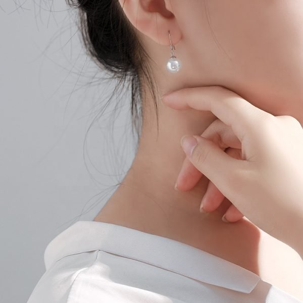 женско ухо с висяща сребърна перлена обеца