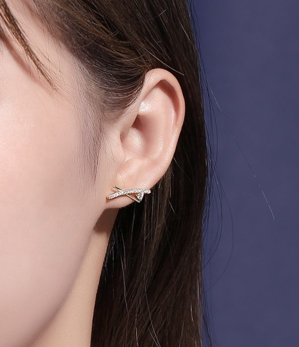 ladies ear with beautiful intersecting silver earring and small crystals