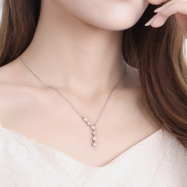 ladies model wearing a unique silver necklace with six small crystal stars