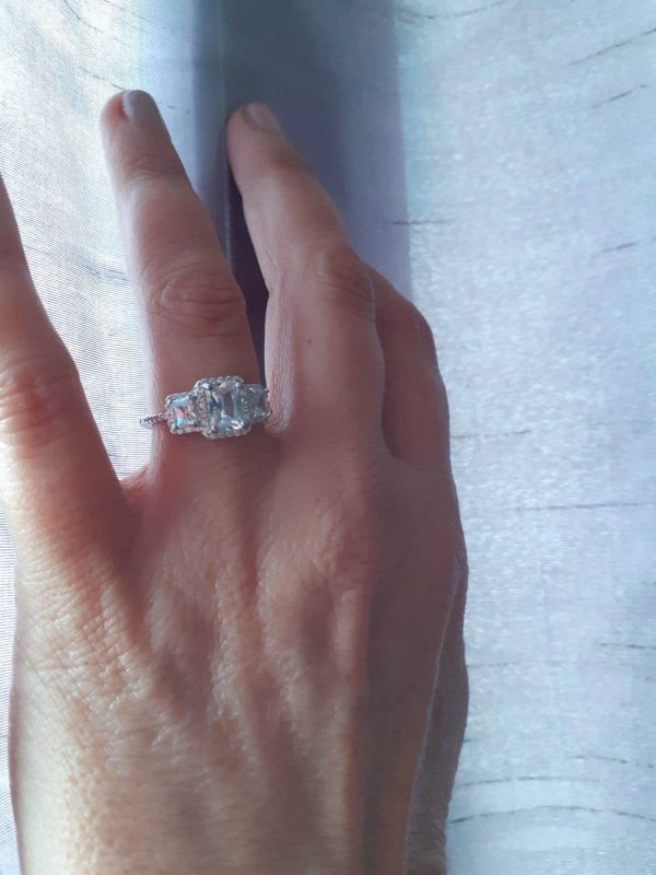 ladies hand with silver ring with three massive cubic zircons on it
