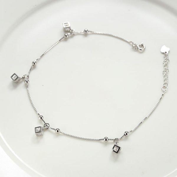 Сребърна гривна за крак с 4 малки висулки снимана върху бяла повърхност отгоре